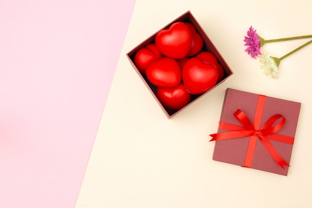 Flat lay of red heart in gift box and flowers on pink and yellow pastel background