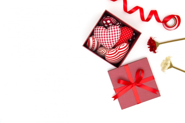 Flat lay of red pillows heart in gift box, ribbon and flowers with copy space.
