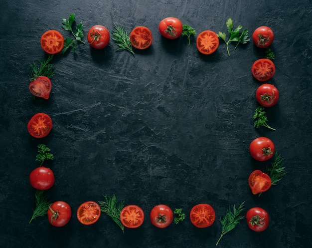 Flat lay of red ripe tomatoes lies in form of frame on dark background with green parsley and dill.
