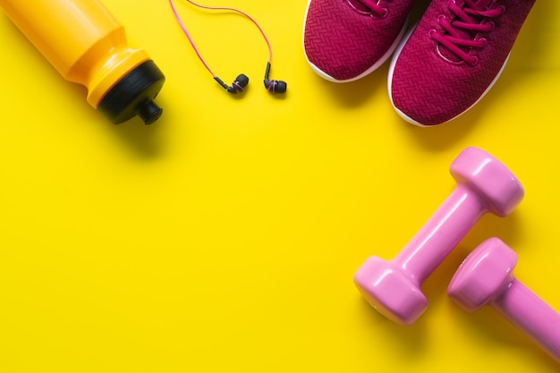 Flat lay of red sport shoes, pink dumbbells, earphones, bottle of water on yellow  backgro