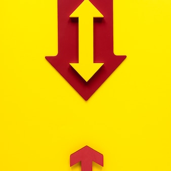 Flat lay red and yellow arrows on yellow background