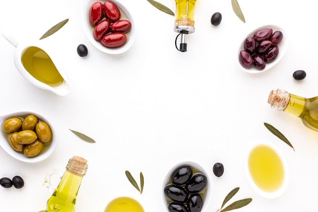 Flat lay red yellow black olives in spoons with oil bottles and copy space