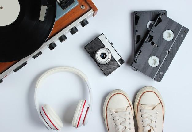 Плоские лежали объекты поп-культуры в стиле ретро 80-х. виниловый проигрыватель, наушники, видеокассеты, пленочная камера, кроссовки на белом фоне. вид сверху