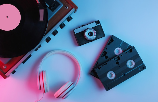 Flat lay retro 80s pop culture objects. vinyl player, headphones, video tapes, film camera with gradient neon blue-pink light