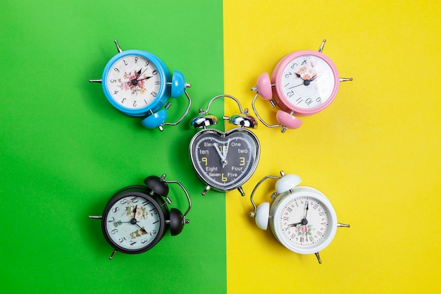 Flat lay retro beautiful new alarm clock on sweet colorful paper pastel color background