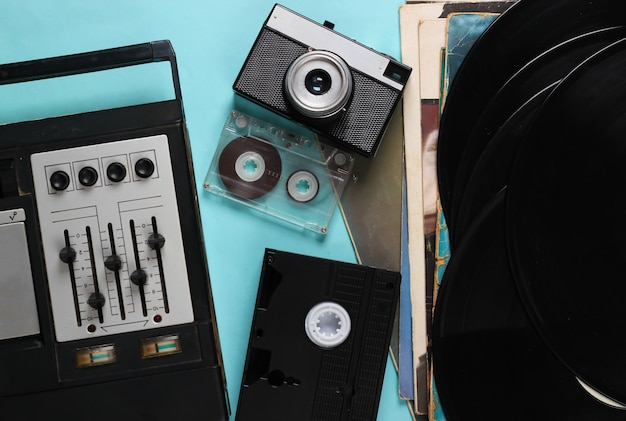 Flat lay retro media composition. equalizer tape recorder, vinyl records, camera, video and audio cassette on blue