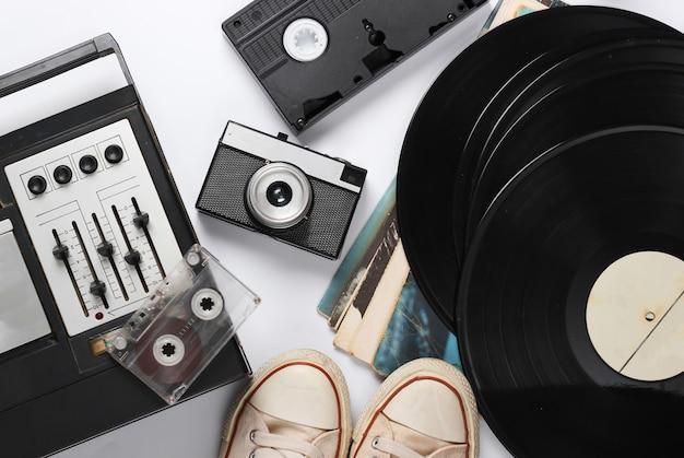 フラットレイレトロメディア構成。イコライザーテープレコーダー、ビニールレコード、昔ながらのスニーカー、カメラ、白のビデオカセット