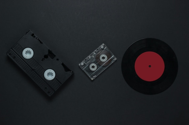 Flat lay retro media and entertainment. vinyl record, audio cassette, vhs on black background. 80s. top view