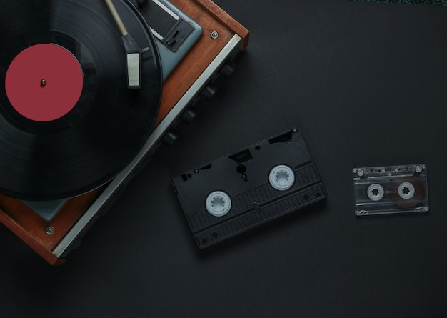 Flat lay retro media and entertainment. vinyl record player with vinyl record, audio cassette, vhs on black background. 80s. top view