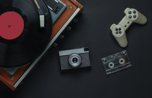 Flat lay retro media and entertainment. vinyl record player with vinyl record, film camera, audio cassette, gamepad on a black background. 80s. top view
