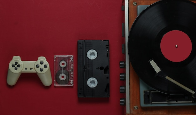 Flat lay retro media and entertainment. vinyl record player with vinyl record, film camera, video cassette, audio cassette, gamepad on red background. 80s. top view