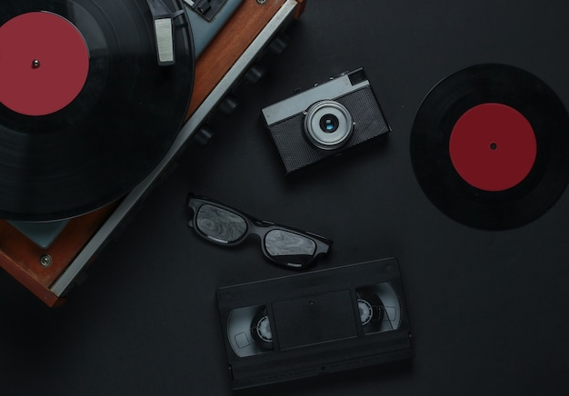 Flat lay retro media and entertainment. vinyl record player with vinyl record, film camera, video cassette on a black background. 80s. top view
