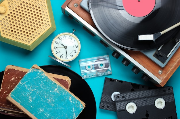 Flat lay retro style attributes, 80s media. vinyl player, video cassettes, audio cassettes, records, radio, vintage alarm clock, old books on blue background.