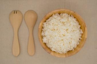 木製のスプーンとフォークのボウルの平らな敷いた米