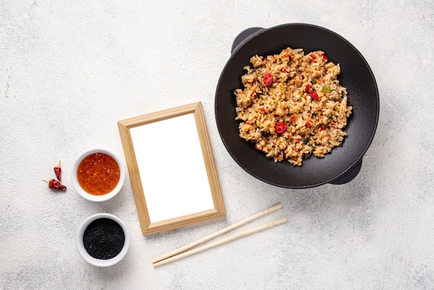 Flat lay rice and vegetables on plate with chopsticks with blank frame