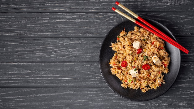 Flat lay rice with vegetables on plate and chopsticks with copy space
