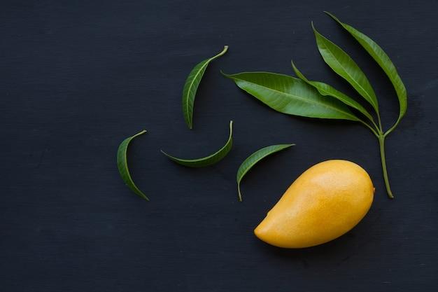 Flat lay of ripe mango fruit with leaf on black background