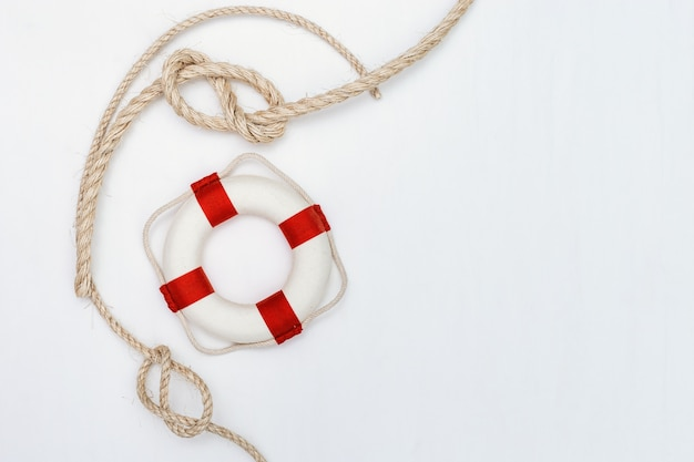 Flat lay of rope with sea knot and life preserver.