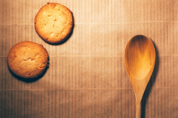 Flat lay round cookies and wooden spoon, on bamboo background