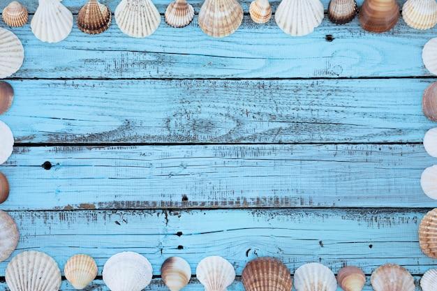 Плоская круглая рамка из ракушек на деревянной доске
