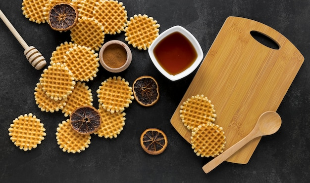 Flat lay of round waffles with honey dipper and dried citrus
