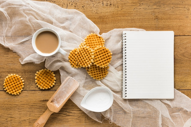 Flat lay of round waffles on wooden surface with notebook and coffee