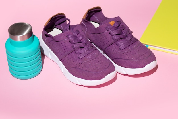 Flat lay running fitnessblue water bottle, diary green and purple sneakers on a pink background