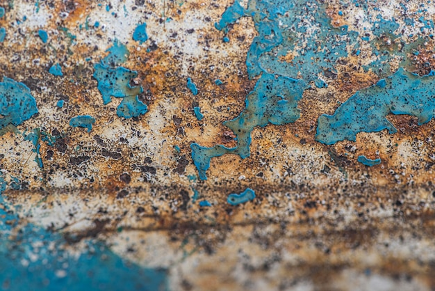 Flat lay of rusty metal surface with paint peel