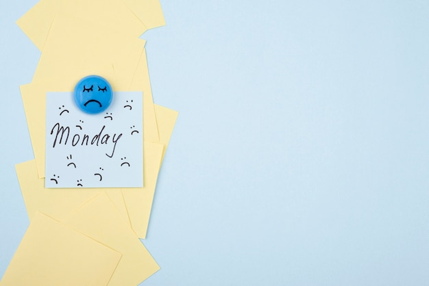 Flat lay of sad face with sticky note and copy space for blue monday