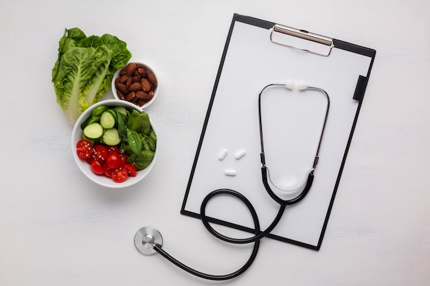 Flat lay of salad bowl and stethoscope