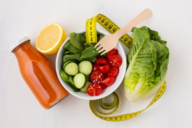 Flat lay of salad and juice bottle