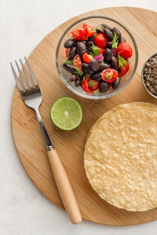 Flat lay salad with black beans and tortillas