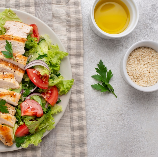 Flat lay salad with chicken, sesame seeds and oil