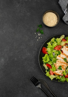 Flat lay salad with chicken and sesame seeds with copy-space