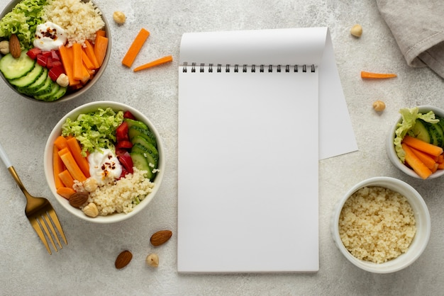 Flat lay salad with couscous and blank notepad