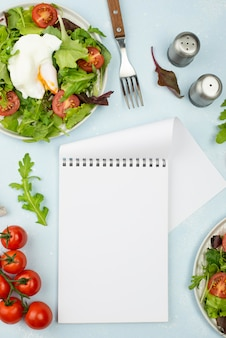 Flat lay salad with fried egg and tomatoes with blank notepad