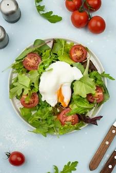 Insalata piatta con uovo fritto e pomodori