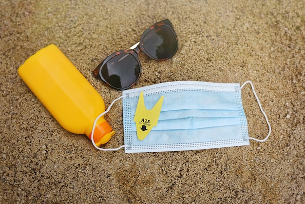 Flat lay on sand and beach objects in covid-19