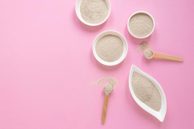 ピンクの背景に平らな砂を置く