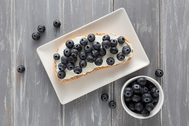 Flat lay sandwich with cream cheese and blueberries on plate