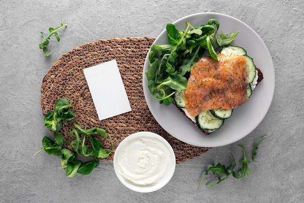 Плоский бутерброд с огурцами и лососем на тарелке с пустым прямоугольником