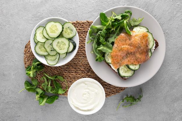 Плоский бутерброд с огурцами и лососем на тарелке со шпинатом