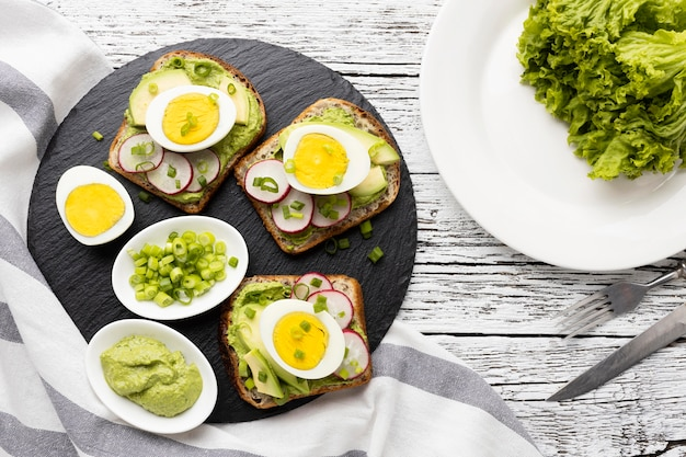 Flat lay of sandwiches with egg and avocado on slate