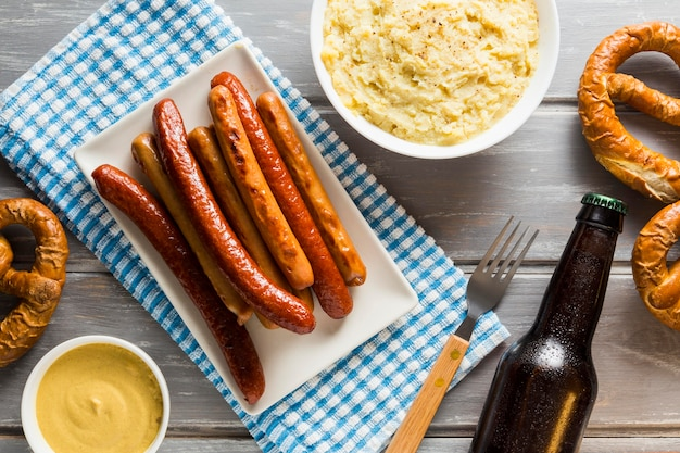 Flat lay of sausages with pretzels with beer bottle