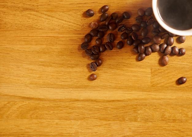 フラットレイ。木製のテーブルの上の芳香のあるブラックコーヒーのテイクアウトカップの横に散らばった焙煎コーヒー豆。コピースペースのある上面図