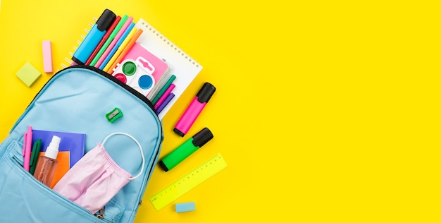 Flat lay of school essentials with backpack and colored pencils