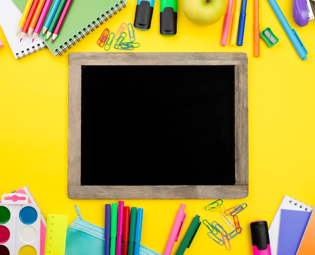 Flat lay of school essentials with blackboard and apple
