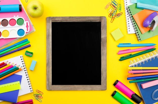 Disposizione piana degli elementi essenziali della scuola con la lavagna e le matite colorate