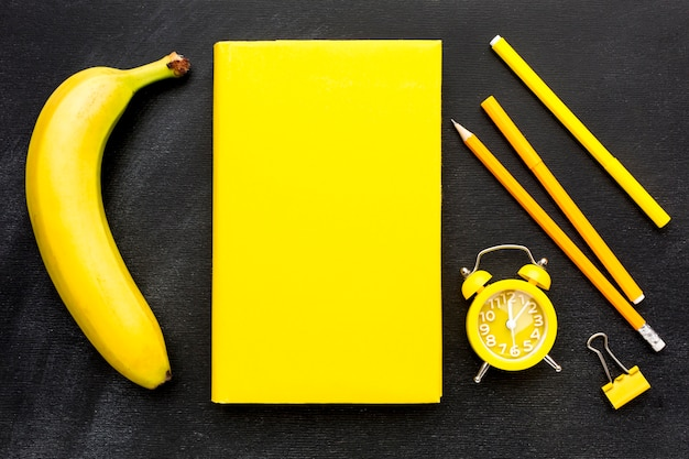 Flat lay of school essentials with book and clock