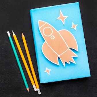 Disposizione piana degli elementi essenziali della scuola con il libro e le matite